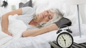 woman sleeping in bed next to an alarm clock