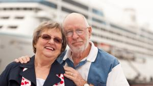 Couple smiles in front of cruise ship