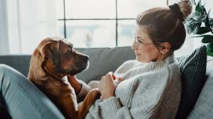 Woman cuddles her dog