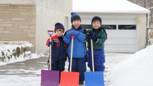 Brothers shoveling snow at home