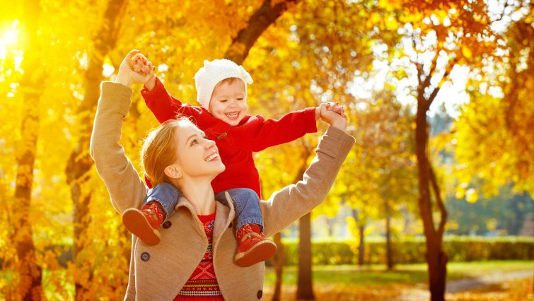 Mother and child play in Fall Trees
